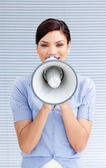 Positive businesswoman yelling through a megaphone — Stock Photo