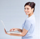 Cheerful businesswoman using a laptop — Stock Photo