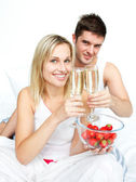 Couple toasting with champagne and strawberries to an engagement — Stock Photo