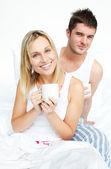 ベッドで朝食を持っているカップル — ストック写真