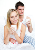 Couple in pyjamas drinking coffee in bed — Stock Photo