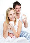 Par de pijamas bebiendo café en la cama — Foto de Stock