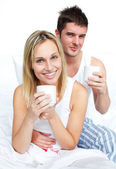 Couple drinking coffee in bed and smiling at the camera — Stock Photo