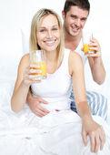 Boyfriend and girlfriend drinking orange juice in bed — Stock Photo
