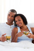 Intimate couple drinking a cup of tea on their bed — Stock Photo