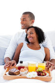 Enamoured couple having breakfast lying on their bed — Stock Photo
