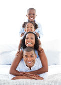 Animated family having fun lying down on bed — Stock Photo