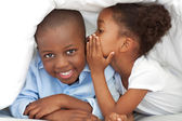 Cute little girl whispering something to her brother — Stock Photo