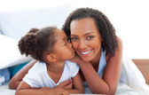Loving little girl woman kissing her mother lying down on bed — Stock Photo