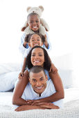 Blissful family having fun lying down on bed — Stock Photo