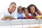 Animated family playing video game lying down on bed — Stock Photo