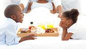 Happy family having breakfast in the bedroom — Stock Photo