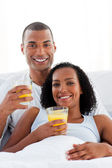 Enamored couple drinking lying on their bed — Stock Photo