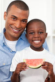 Portrait of a smiling boy eating fruit with his father — Stok fotoğraf