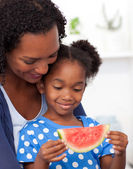 Beautiful girl eating watermelon with her mother — Stock Photo