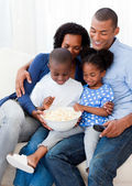 Happy family eating popcorn and watching TV — Stock Photo