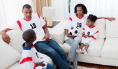 Afro-american family watching a football match — Stock Photo