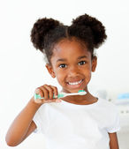 Portrait of an Afro-american girl brushing her teeth — Stock Photo