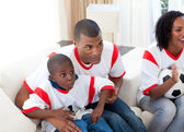 Happy family watching a football match — Stock Photo