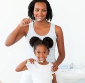Mother and her daughter brushing their teeth — Stockfoto