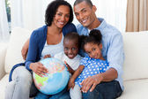 Afro-american family holding a terrestrial globe — Stock Photo
