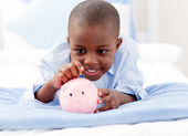 Young Boy on a bed putting money into a piggy bank — Stock Photo