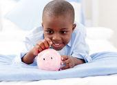 Ung pojke på en säng att lägga pengar i en spargris — Stockfoto