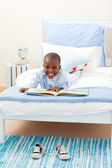 Smiling little boy reading a book — Stock Photo