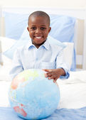 Cute little boy holding a terrestrial globe — Stock Photo