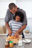 Happy father slicing bread with his son — Stock Photo