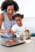 Afro-american little girl preparing biscuits with her mother — Stock Photo