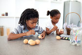 Concentrated Afro-american siblings painting eggs — ストック写真