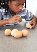 Cute Afro-american little boy painting eggs — Foto de Stock