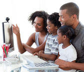 Afro-American family working with a computer at home — Stock Photo