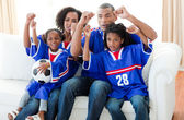 Excited Afro-American family watching a football match — Stock Photo