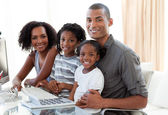 Happy Afro-American family working with a computer at home — Stock Photo