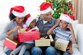 Família afro-americana feliz jogando com natal apresenta — Foto Stock