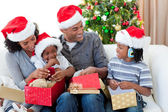 Happy Afro-American family opening Christmas presents — Stock Photo