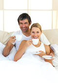 Enthusiastic lovers drinking coffee lying in the bed — Stock Photo