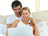 Jolly couple buying on internet — Stock Photo