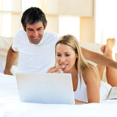 Assertive woman using a laptop lying on bed — Stock Photo