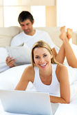 Pretty woman using a laptop lying on bed — Stock Photo
