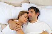 Caring lovers sleeping lying in the bed — Stock Photo