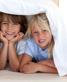 Smiling siblings playing undercovers — Stock Photo