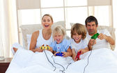 Loving family playing video game in the bedroom — Stock Photo