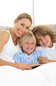 Attractive mother and her children reading book — Stock Photo