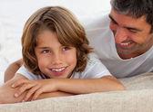 ładny chłopiec trochę zabawy z ojcem, leżąc na łóżku — Zdjęcie stockowe