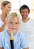 Blond child singing with a microphone — Stock Photo