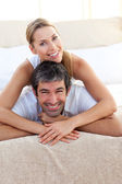 Enamoured couple lying on the bed — Stock Photo