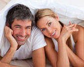 Enamoured couple having fun lying on bed — Foto de Stock